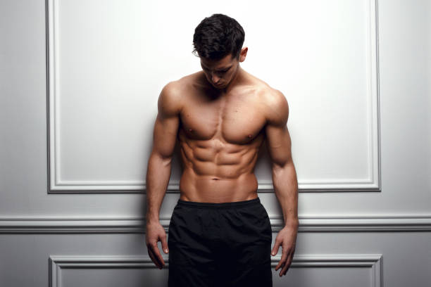 Cool man at the white wall Stylish shirtless man at the white wall looking down, Horizontal studio shot. shirtless male models stock pictures, royalty-free photos & images