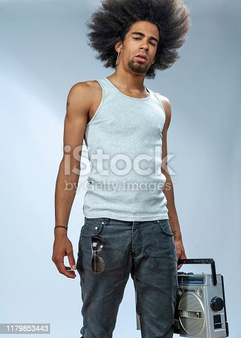 Cool man carrying Ghetto blaster, looking at the camera, serious, studio shot, low angle view