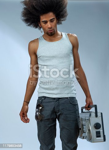 Cool man carrying Ghetto blaster, looking down, serious, walking studio shot, low angle view