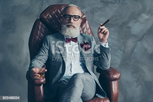 istock Cool man in glasses, hold cigarette,  glass with brandy, in formal wear, tux with red bowtie and pocket square, sit in leather chair over gray background, looking to the camera, shares, stock, money 925466034