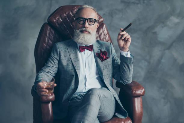 cool man in bril, houd sigaretten, glas met brandy, in formele slijtage, tux met rode bowtie en zak plein, zitten in lederen stoel over grijze achtergrond, op zoek naar de camera, aandelen, voorraad, geld - guy with cigar stockfoto's en -beelden