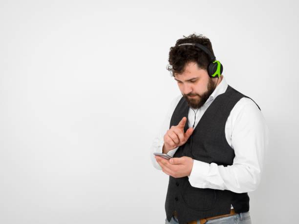 cooler Mann posiert mit Kopfhörer und Smartphone vor weißem Hintergrund – Foto