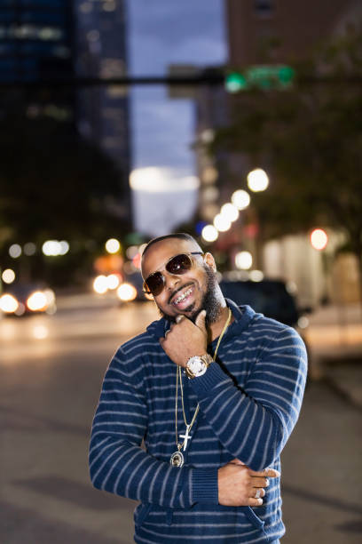 Cool man on city street, sunglasses at night, gold grill An African-American man with bling bling, standing on a city street at dusk, looking at the camera through sunglasses, smiling to reveal his gold grillz. gold teeth bling stock pictures, royalty-free photos & images