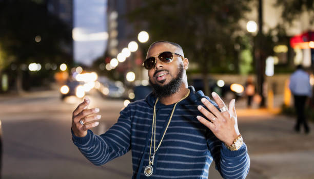 Cool man on city street, sunglasses at night, gold grill An African-American man with bling bling, standing on a city street at dusk, gesturing and looking at the camera through sunglasses, smiling to reveal his gold grillz. gold teeth bling stock pictures, royalty-free photos & images