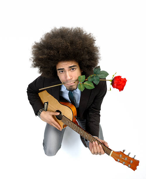 cool man playing romantic serenade on guitar high angle view on a cool man with big afro hair having a red rose between his teeth is playing on a guitar looking up at the camera on white background serenading stock pictures, royalty-free photos & images