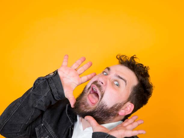 cooler Mann posiert vor orangefarbenem Hintergrund – Foto