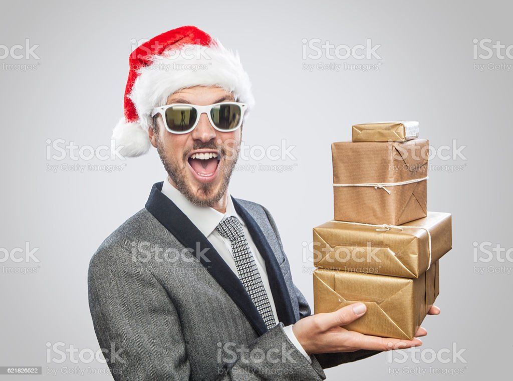 Cool man with Santa Claus hat and sunglasses holding gifts stock photo