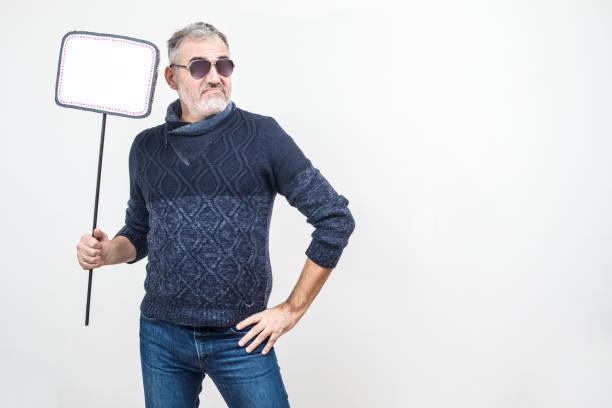 cool reifer mann mit sonnenbrille hält eine leere zeichen, mürrischer gesichtsausdruck - sachenmacher stock-fotos und bilder