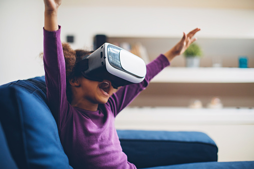 Cool millennial child exploring space with virtual reality glasses