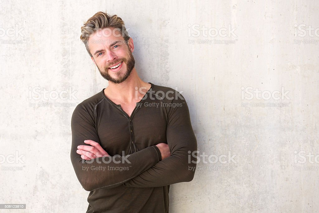 Cool modern man smiling with arms crossed stock photo