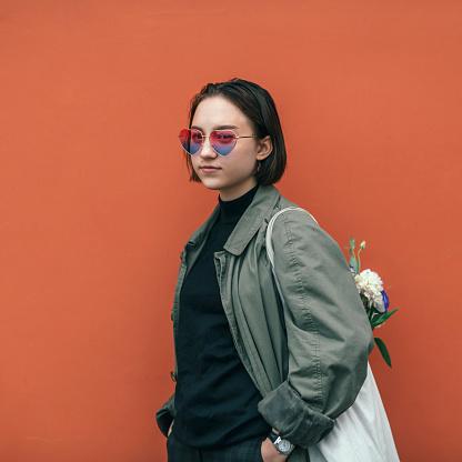 Cool modern teenage girl wearing heart shape sunglasses on Valentine day