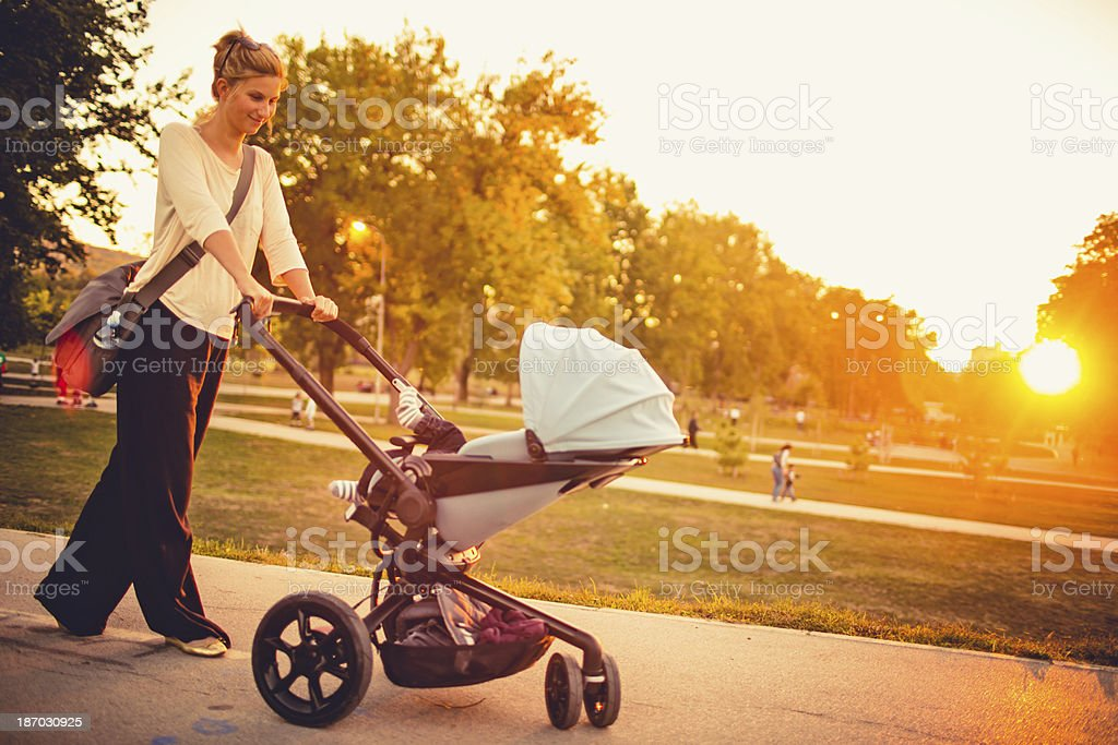 Cool mom pushing buggy outdoors stock photo