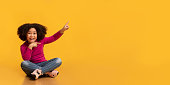 istock Cool Offer. Little black girl sitting on floor and pointing aside 1216750288