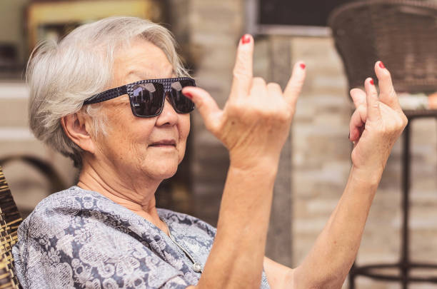 Cool old lady, wearing sunglasses doing the rock sign. Cool old lady, wearing sunglasses doing the rock sign. grandmother stock pictures, royalty-free photos & images