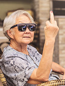 Cool old lady, wearing sunglasses, expressing herself showing the middle finger.