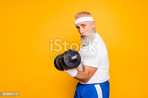 istock Cool playful flirty naughty strong grandpa with confident grimace exercising holding equipment up, lifts it with strength and power. Body care, fitness, body building, hobby, weight loss lifestyle 928902122