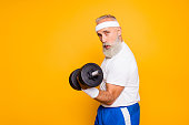 Cool playful flirty naughty strong grandpa with confident grimace exercising holding equipment up, lifts it with strength and power. Body care, fitness, body building, hobby, weight loss lifestyle