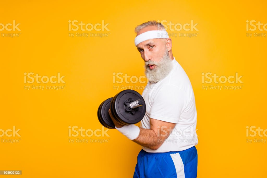 Cool playful flirty naughty strong grandpa with confident grimace exercising holding equipment up, lifts it with strength and power. Body care, fitness, body building, hobby, weight loss lifestyle - foto stock
