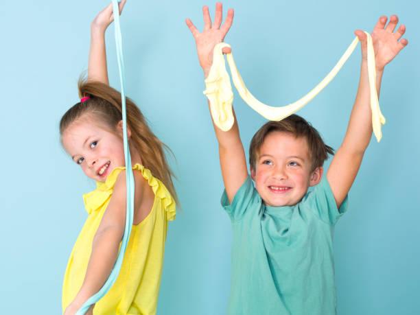 cool, hübscher Junge und seine Schwester spielen mit hausgemachtem Schleim vor blauem Hintergrund und haben viel Spaß – Foto