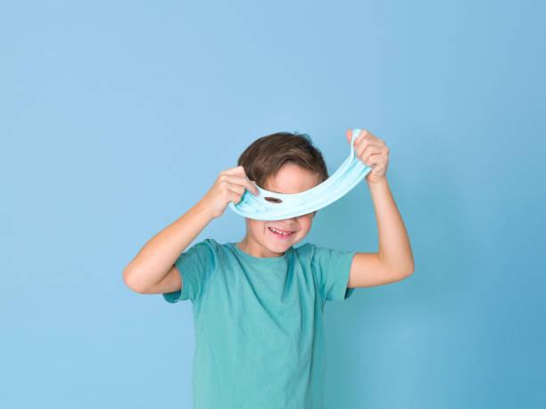 Cooler, hübscher Junge spielt mit selbstgemachtem Schleim vor blauem Hintergrund – Foto
