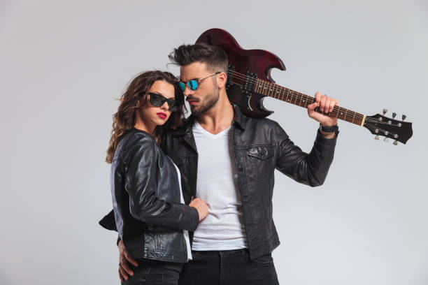 cool punk man holding guitar on shoulder and embracing woman - rock musician stock pictures, royalty-free photos & images