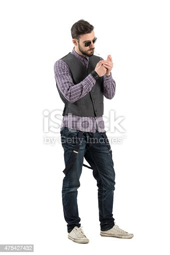 istock Cool relaxed fashionable man lighting up cigarette 475427432