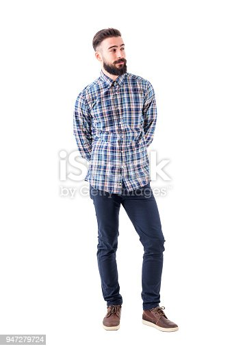 931173966istockphoto Cool relaxed flirty bearded man with hands behind back judging and looking away. 947279724
