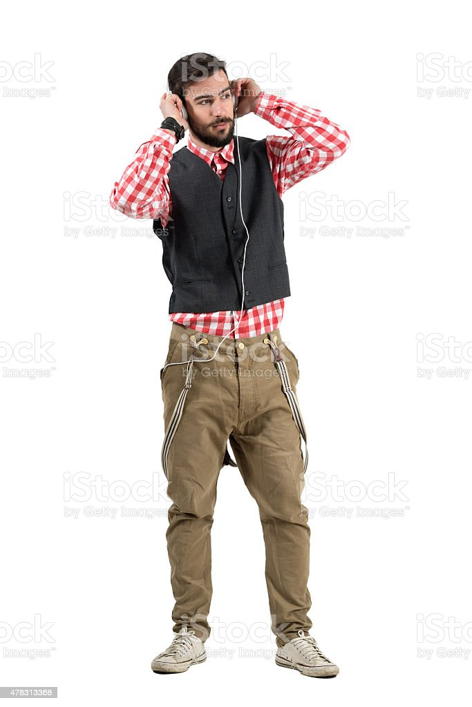 Cool relaxed hipster holding headphones while listening to music stock photo