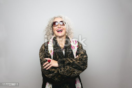 Cool mature woman,wearing sunglasses and a coat made from artificial fur, wearing scarf with floralpattern and a lot of jewellery, she is standing in front of grey background,looking into camera,smiling