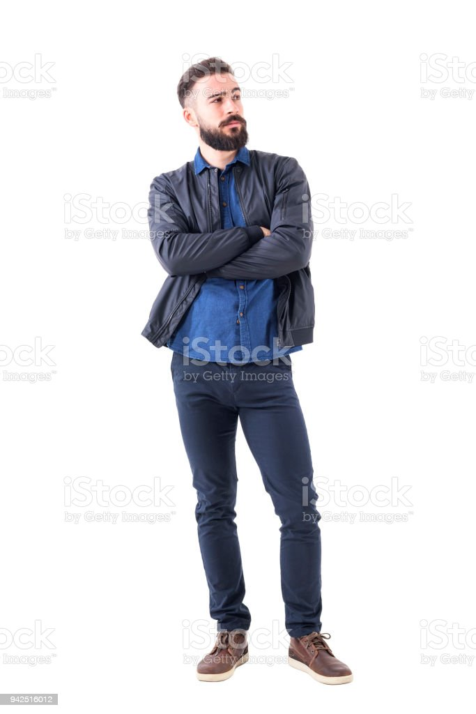Cool skeptical bearded young man with crossed arms looking away. stock photo