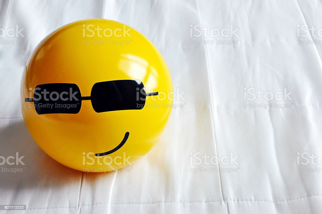 Cool smiley yellow bed lamp ball with sunglasses stock photo