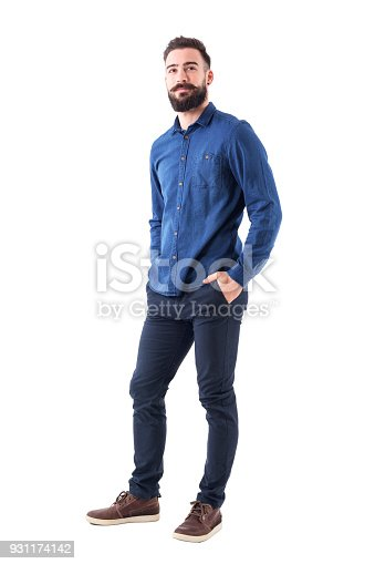 931173966istockphoto Cool smiling guy, with hands in pockets looking up wearing blue denim shirt and pants 931174142
