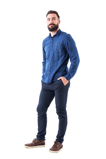 931173966 istock photo Cool smiling guy, with hands in pockets looking up wearing blue denim shirt and pants 931174142