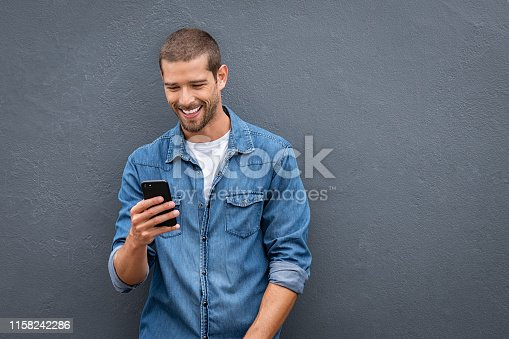 Young man leaning against a grey wall using mobile phone with copy space. Happy casual guy messaging on smartphone on gray background. Cheerful man looking down while typing and reading a message on cell phone.