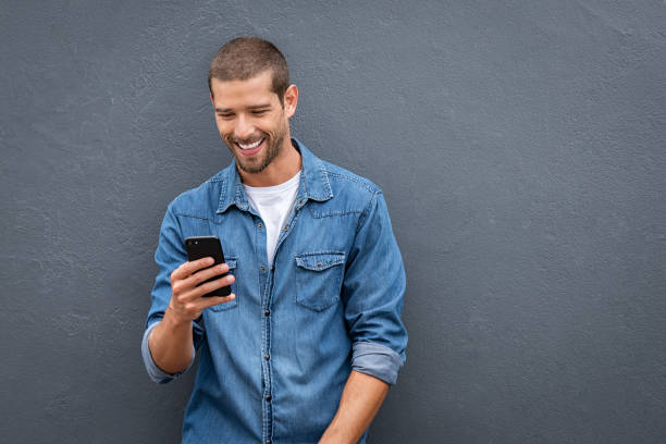 Cool smiling man using smartphone on grey wall Young man leaning against a grey wall using mobile phone with copy space. Happy casual guy messaging on smartphone on gray background. Cheerful man looking down while typing and reading a message on cell phone. men stock pictures, royalty-free photos & images