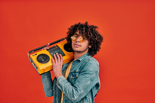 Waist up portrait of young eastern man holding tape music player on shoulder. Cool stylish boy with beat box on isolated red background