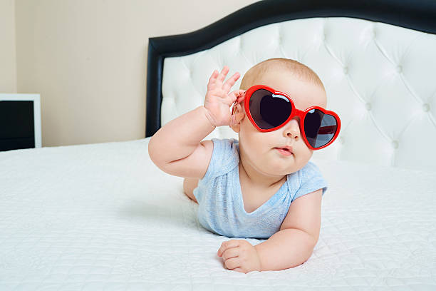 Cool super child.  Funny baby boy in solar glasses red stock photo