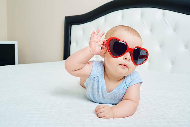 cool super child.  funny baby boy in solar glasses red - sonnenbrille kleinkind stock-fotos und bilder