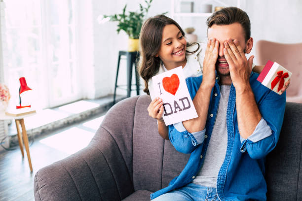 Cool surprise from daughter. I love you, dad. Handsome young man at home with his little cute girl. Happy Father's Day! fathers day stock pictures, royalty-free photos & images