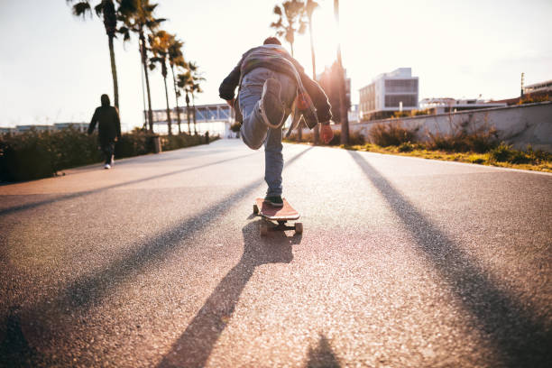 Cool teenage boy skateboarding in urban park as a hobby stock photo