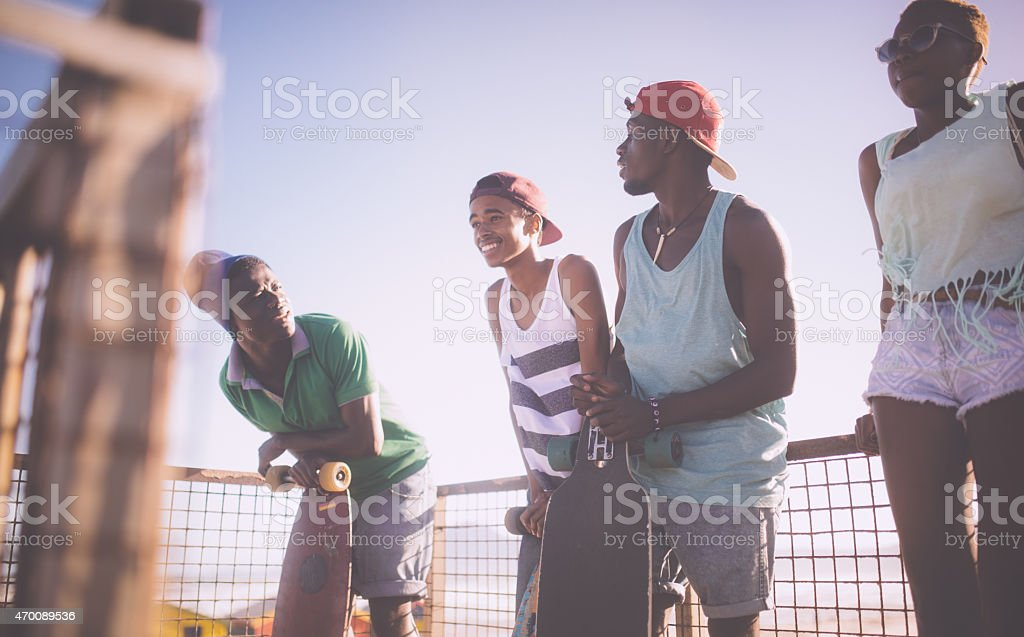 Cool teenage longboarder smiling and talking with friends stock photo