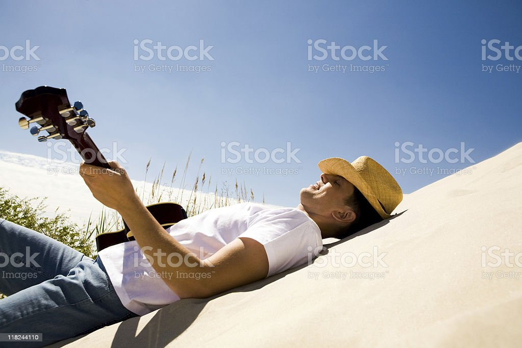 Cool time Image of happy man in cowboy hat playing the guitar while relaxing on sandy beach Adult Stock Photo