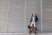 Cool woman with her dog posing in full length portrait. metal building background