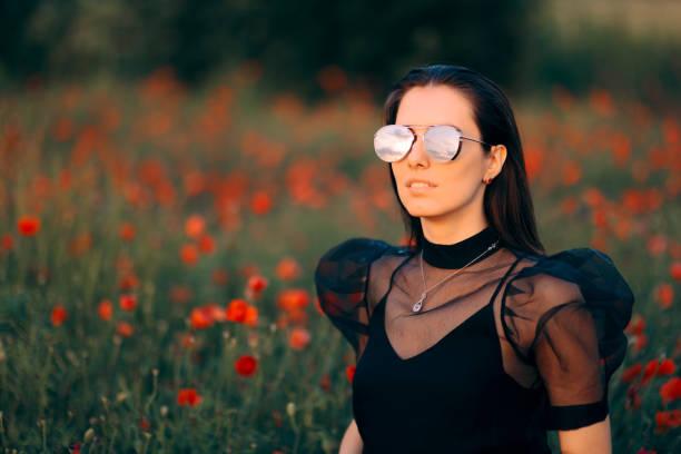 coole frau mit trendiger sonnenbrille in einem feld von mohnblumen - frisuren für schulterlanges haar stock-fotos und bilder