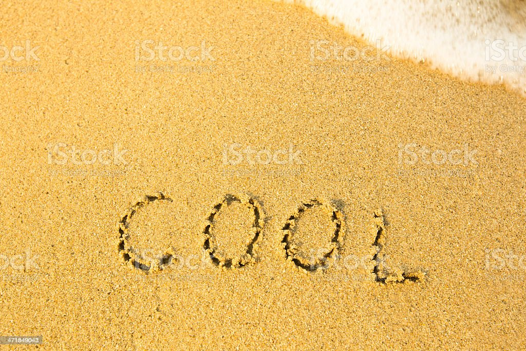 Cool - written in sand on beach texture royalty-free stock photo