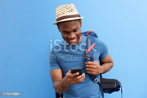 Portrait of cool young african american guy with bag and cellphone against blue background