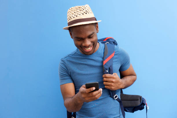 cool young african american guy with bag and cellphone against blue background Portrait of cool young african american guy with bag and cellphone against blue background building feature stock pictures, royalty-free photos & images