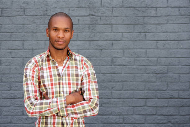 cool young african man standing by gray wall with arms crossed Portrait of cool young african man standing by gray wall with arms crossed plaid shirt stock pictures, royalty-free photos & images