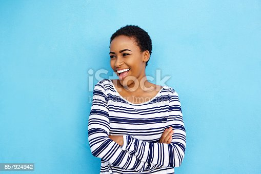istock cool young black woman laughing against blue wall 857924942