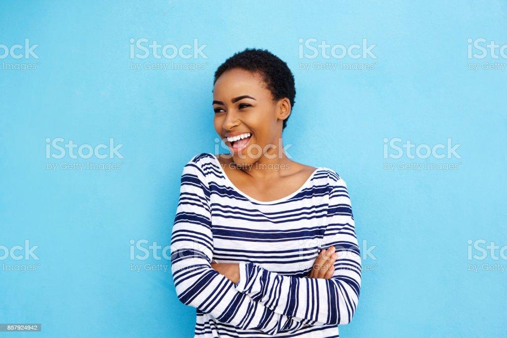 cool jeune femme noire en riant contre mur bleu - Photo